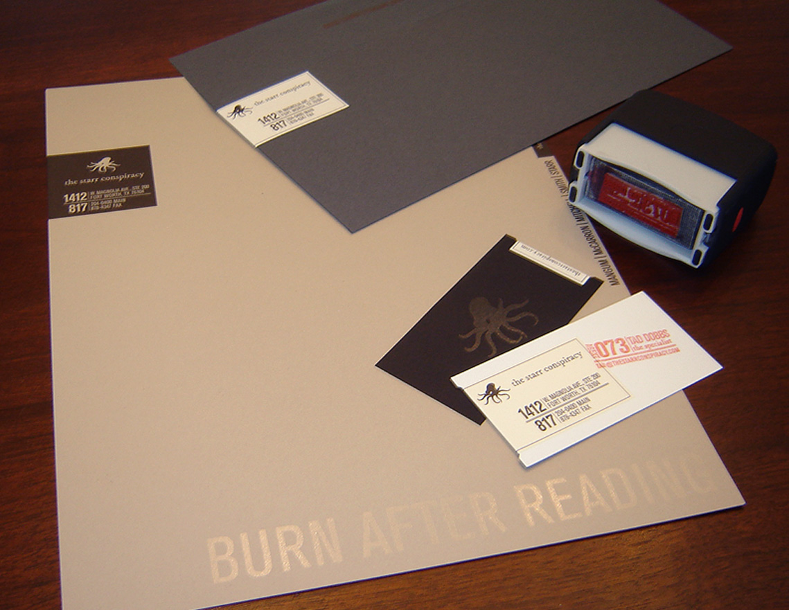 The Starr Conspiracy stationery featuring a dark gray number ten business envelope, letterhead, business card and rubber stamp